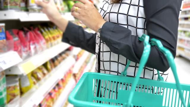 vídeos de stock, filmes e b-roll de movimento lento da cena da compra asiática da mulher nova no supermercado, conceito do estilo de vida na cidade - comida de bebê