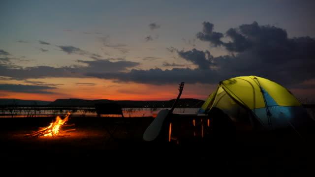 夏休みに湖の近くで焚き火とキャンプテントのシーンスローモーション。くつろぎのひととき。自然な日常生活のコンセプト屋外 - キャンプファイヤー点の映像素材/bロール