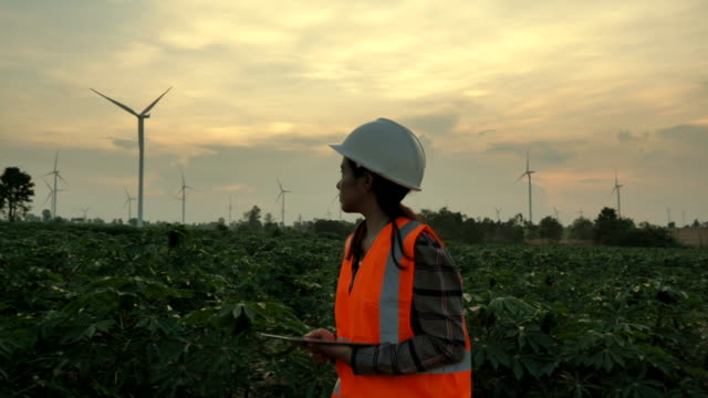 Scene slow motion of engineer asian woman using the tablet to evaluate a wind turbine, Concept of Renewable energy plants