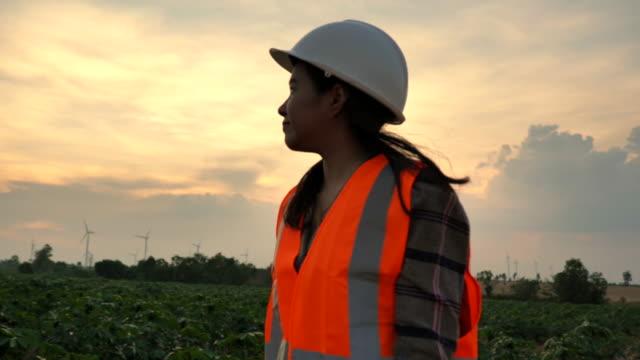 vidéos et rushes de mouvement lent de scène de femme asiatique d'ingénieur utilisant la tablette pour évaluer une éolienne, concept des usines d'énergie renouvelable - ingénieur