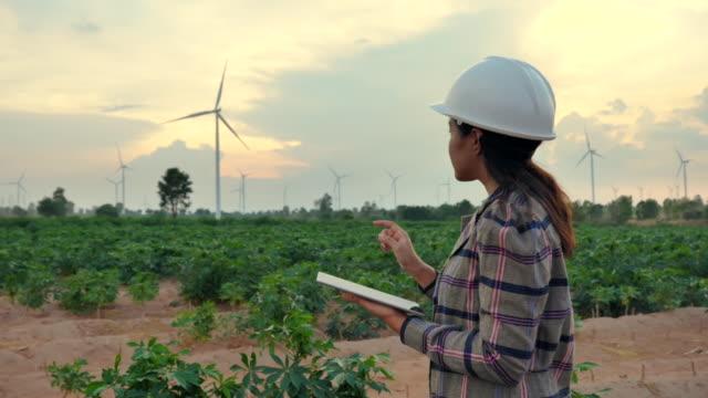 風力タービンを評価するためにタブレットを使用してエンジニアアジアの女性のシーンスローモーション,再生可能エネルギープラントの概念 - 持続可能な開発点の映像素材/bロール