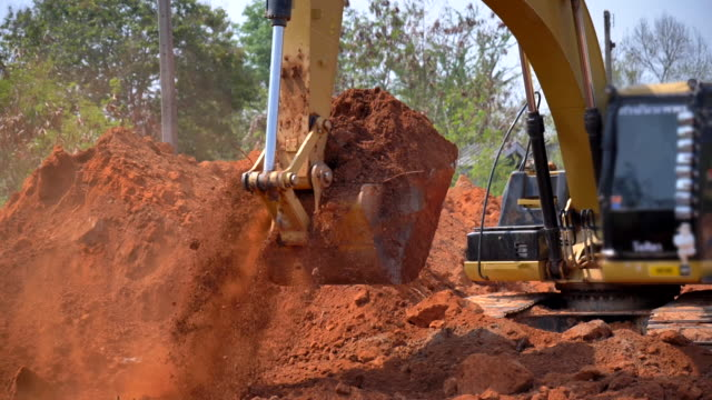 scene slow motion of excavator bucket digging into the soil at the sunny construction sit - earth mover stock videos & royalty-free footage