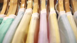 Scene slow motion of many shirts on hanger in store of shopping center