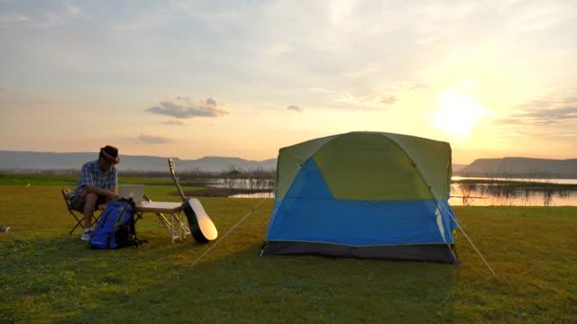 szene zeitlupe von senior asiatische männliche mit laptop auf camping in der nähe des sees ist entspannend und genießen blick in der nähe des sees in den sommerferien. er ist glücklich und spaßig im urlaub, entspannung moment - camping stock-videos und b-roll-filmmaterial