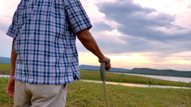 湖の近くで自然を眺め、歩くケーンと一緒に歩く先輩アジア人男性のシーンスローモーション、彼は幸せで休日、リラクゼーションの瞬間を楽しんでいます。屋外でのシニア自然の日常生活� - 草原点の映像素材/bロール