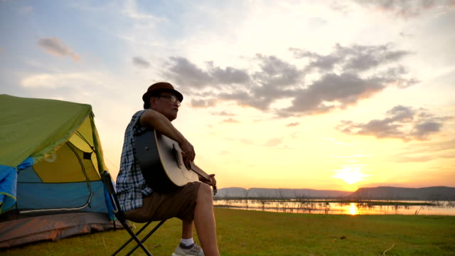 szenen-sollenbewegung des ranghohen asiatischen mannes spielt gitarre und genießt in den sommerferien den blick in die nähe des sees. er ist glücklich und hat spaß am urlaub, entspannungsmoment. konzept des seniorenalltags im freien - besonderes lebensereignis stock-videos und b-roll-filmmaterial