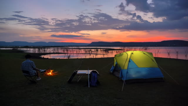 scene slow motion of senior asian man is sitting near tent and enjoying a campfire view near the lake in the summer holidays.he is happy and have fun on holidays, relaxation moment. concept of senior natural everyday life outdoors - tent stock videos and b-roll footage