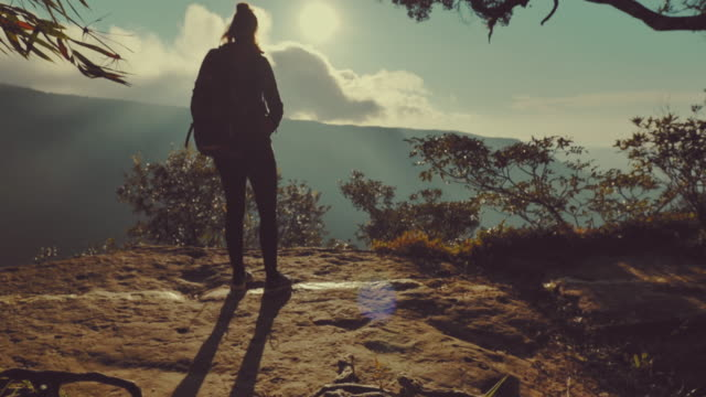 scene slow motion of woman standing on top of mountain, enjoying breathtaking view at sunset - sports clothing stock videos & royalty-free footage