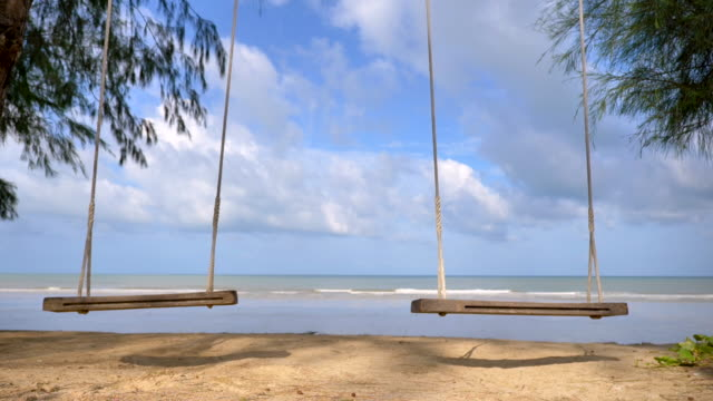 vídeos de stock e filmes b-roll de scene slow motion of wooden swing on tropical beach in thailand, nature background - dois objetos