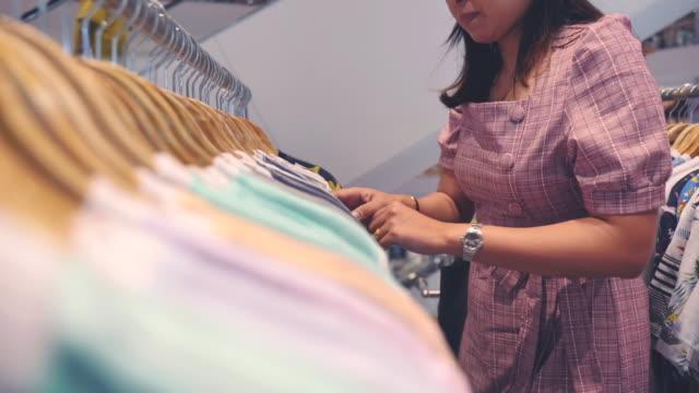 stockvideo's en b-roll-footage met scène slow motion van jonge aziatische vrouw winkelen in kledingwinkel in winkelcentrum, concept van vakantie einde van de week, levensstijl van aziatische vrouw - kledingrek