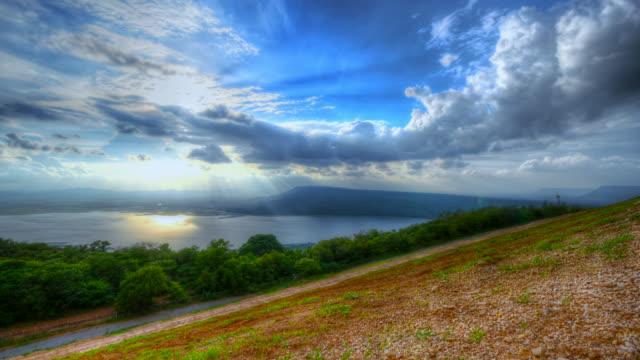 szene zeitraffer von wolke und dramatischen himmel mit sonnenuntergang über see, natur hintergrund - jahreszeit stock-videos und b-roll-filmmaterial