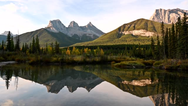 scenery of three sisters mountains reflection on pond in autumn valley at canmore, banff national park - national park stock videos & royalty-free footage