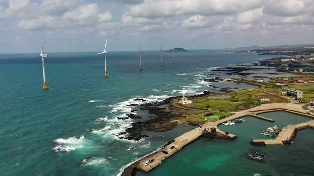 vidéos et rushes de scenery of village near wind turbines in sea / jeju-si, jeju-do, south korea - être ancré