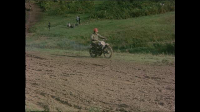 scenes at a motor cycle scrambling or motocross event in england with vintage motorcycles scrambling over muddy terrain circa 1965 - scrambling bildbanksvideor och videomaterial från bakom kulisserna