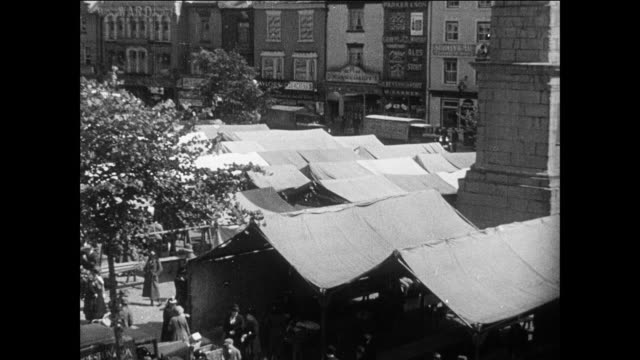montage scenes from bustling british town filled with people, markets, buildings and a maze of streets / england, united kingdom - 1935 stock videos & royalty-free footage