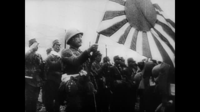 vídeos de stock e filmes b-roll de / scenes from japanese propaganda films showing their various victories and military strengths / japanese soldier holds up japanese flag wwii... - 1942