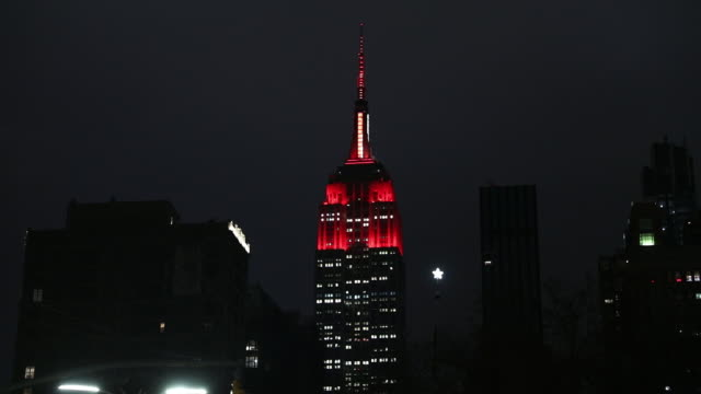 scenes from nearly empty city by night with red illumination of empire state building to represent an emergency vehicle's light in tribute to first... - empire state building stock videos & royalty-free footage
