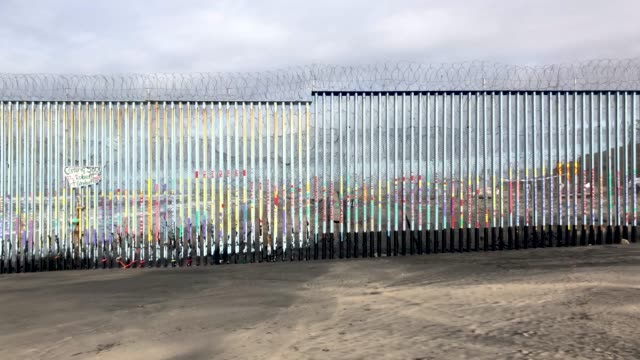 scenes from the border city of tijuana on january 16 2019 in tijuana mexico men deported from america play a guitar in a tent camp and a border wall... - baja california norte stock videos & royalty-free footage