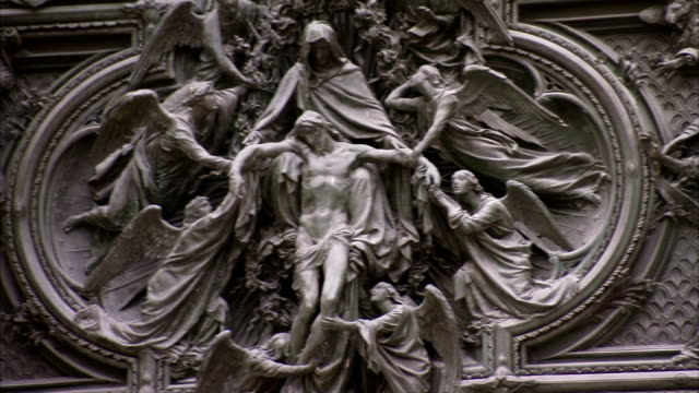 Scenes of archbishops and angels are intricately carved in an exterior wall of the Milan Cathedral. Available in HD.