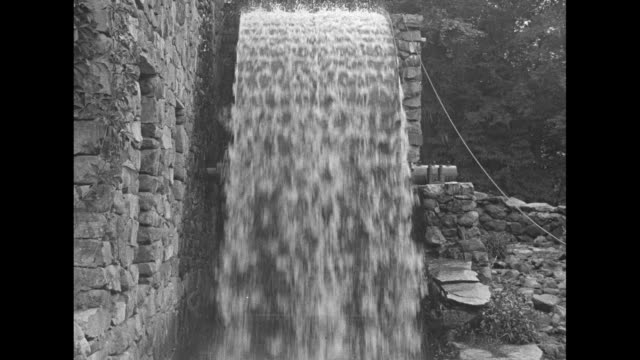 vs scenes of stone watermill with large wheel turning and water splashing below sheep and man with cart and two oxen fording small stream / note... - water wheel stock videos and b-roll footage