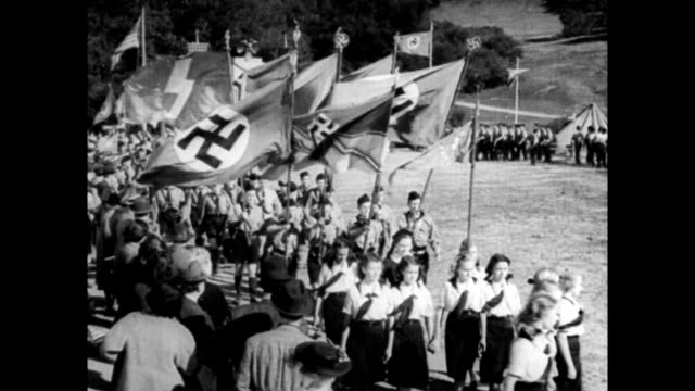 Scenes of various Nazi youth groups in the US including Camp Nordland in New Jersey / young men and women marching with Nazi flags giving Heil Hitler...