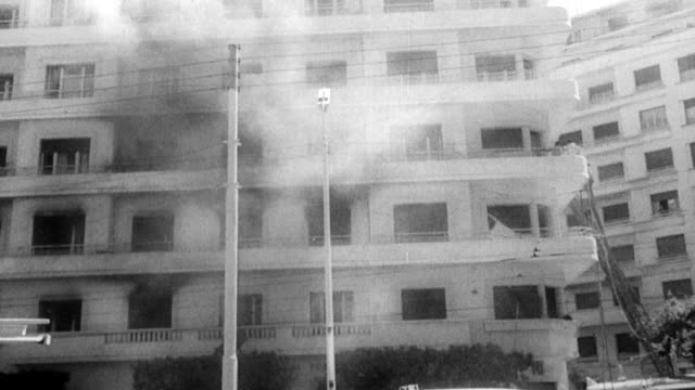 vídeos y material grabado en eventos de stock de / scenes of violence in algeria before elections / people outside a residential building looking at smoke billowing from a window / men try to hose... - 1962