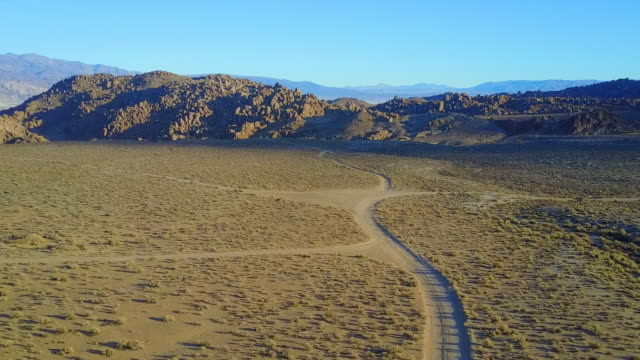 Scenic aerial drone view of dirt road and rocky desert landscape.