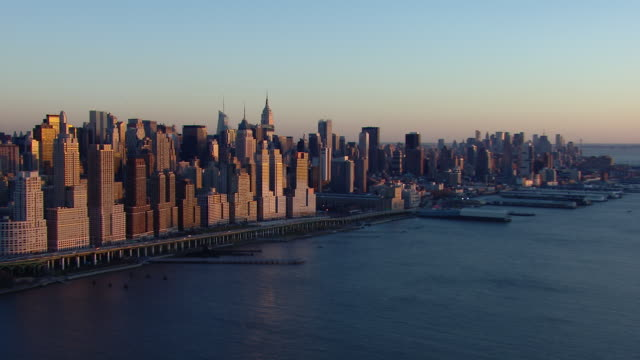 Scenic aerial shot of Manhattan at golden hour, approaching the Hell's Kitchen neighborhood over the Hudson River.
