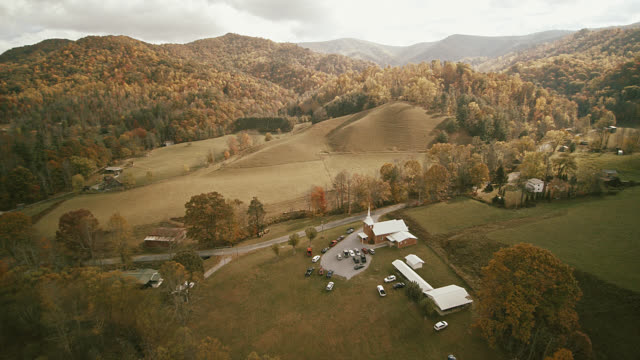 Scenic aerial video with the autumn's scenic view on the small country church in the valley between mountains in Tennessee, USA.