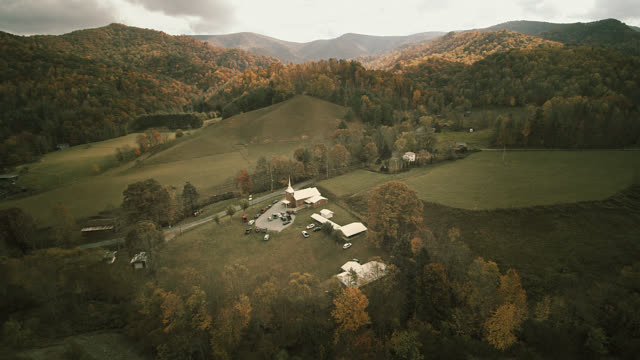 vídeos de stock e filmes b-roll de scenic aerial video with the autumn's scenic view on the small country church in the valley between mountains in tennessee, usa. - tennessee