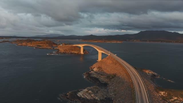 stockvideo's en b-roll-footage met toneelluchtmening van atlantische weg bij zonsondergang - brug mens gemaakte bouwwerken