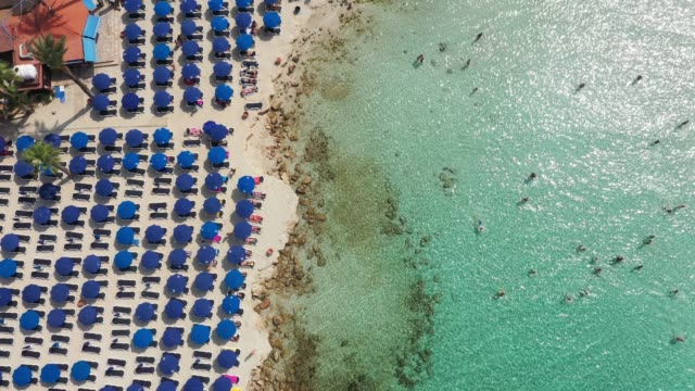 scenic aerial view of beach with blue umbrellas on cyprus - republic of cyprus stock videos & royalty-free footage