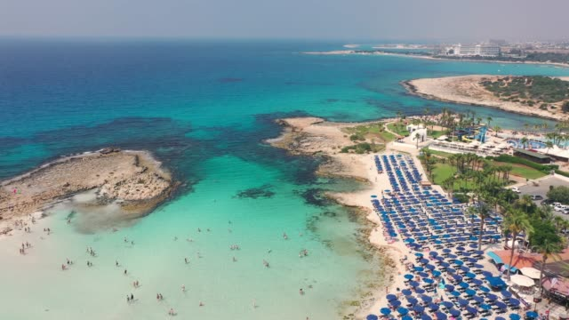 scenic aerial view of beach with blue umbrellas on cyprus - tourist resort stock videos & royalty-free footage