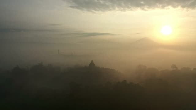 scenic aerial view of borobudur temple at sunrise in fog - theravada stock videos & royalty-free footage