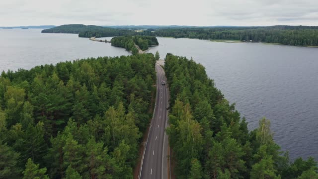 stockvideo's en b-roll-footage met schilderachtige luchtmening van camper met kano op dak op weg door het meer in finland lakeland - finland