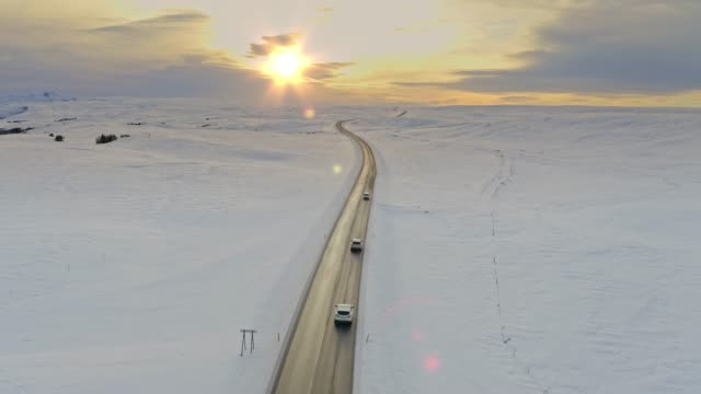 scenic aerial view of cars driving through a winter countryside road at sunset - infinity stock videos & royalty-free footage