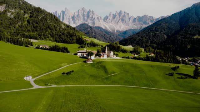 vídeos de stock e filmes b-roll de scenic aerial  view of church  in dolomites alps - alpes europeus