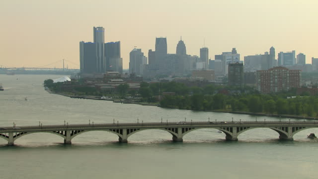 scenic aerial view of downtown detroit with the macarthur bridge spanning the detroit river. - detroit river stock-videos und b-roll-filmmaterial