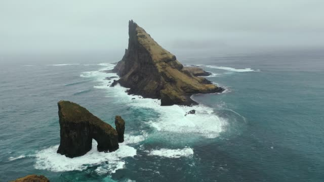 vídeos y material grabado en eventos de stock de vista panorámica del arco drangarnir en las islas feroe - en el borde