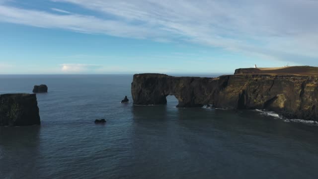 scenic aerial  view of dyrholaey arch in iceland - dyrholaey stock videos & royalty-free footage