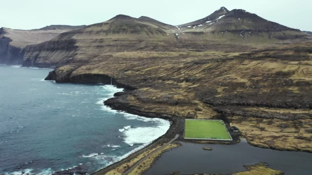scenic aerial view of football field near the sea in faroe islands - pitch stock videos & royalty-free footage