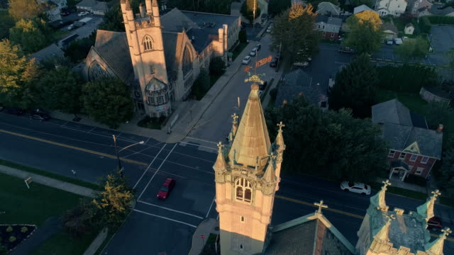 scenic aerial view of nazareth, pennsylvania, with his churches at sunset. aerial drone video with the forward and tilting-down camera motion. neogothic-style st john evangelic lutheran church in the main focus. - evangelicalism stock videos & royalty-free footage