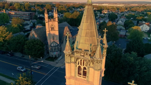 scenic aerial view of nazareth, pennsylvania, with his churches at sunset. aerial drone video with the panoramic and tilting-up camera motion. neogothic-style st john evangelic lutheran church in the main focus. - evangelicalism stock videos & royalty-free footage