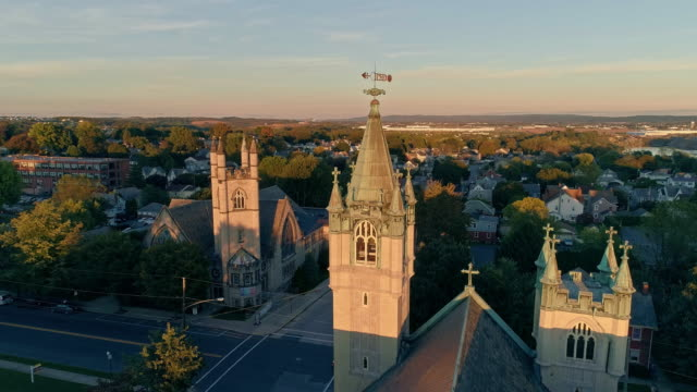 scenic aerial view of nazareth, pennsylvania, with his churches at sunset. aerial drone video with the ascending camera motion. neogothic-style st john evangelic lutheran church in the main focus. - evangelicalism stock videos & royalty-free footage