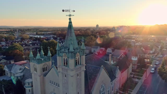 scenic aerial view of nazareth, pennsylvania, with his churches at sunset. aerial drone video with the ascending and tilting-down camera motion. neogothic-style st john evangelic lutheran church in the main focus. - evangelicalism stock videos & royalty-free footage