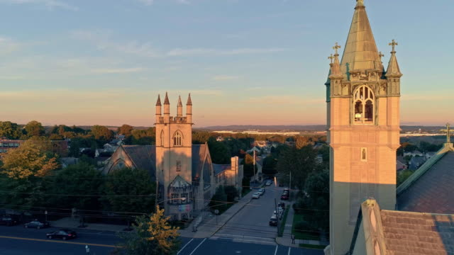 scenic aerial view of nazareth, pennsylvania, with his churches at sunset. aerial drone video with the forward camera motion. neogothic-style st john evangelic lutheran church in the main focus. - evangelicalism stock videos & royalty-free footage