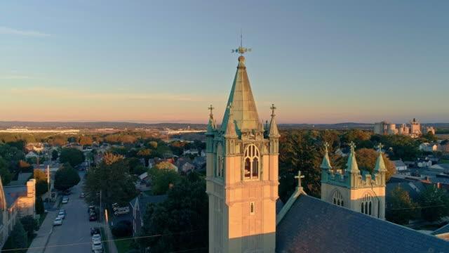日没時に教会があるペンシルベニア州ナザレの風光明媚な航空写真。降下カメラの動きを持つ空中ドローンビデオ。ネオゴシック様式のセントジョン・エヴァンジェリック・ルーテル教会が� - プロテスタント点の映像素材/bロール
