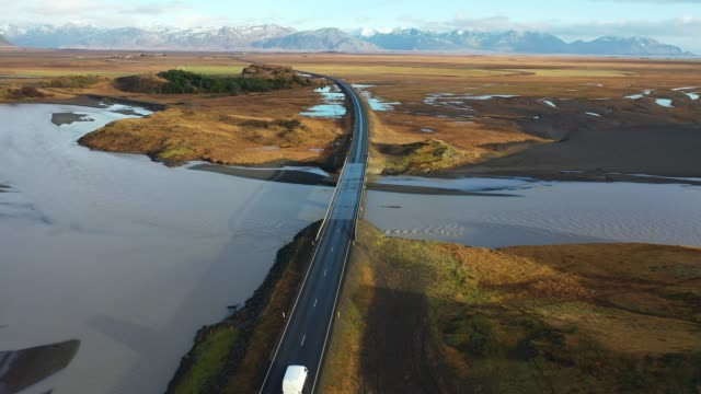 scenic aerial view of road near the river in iceland - van stock videos & royalty-free footage