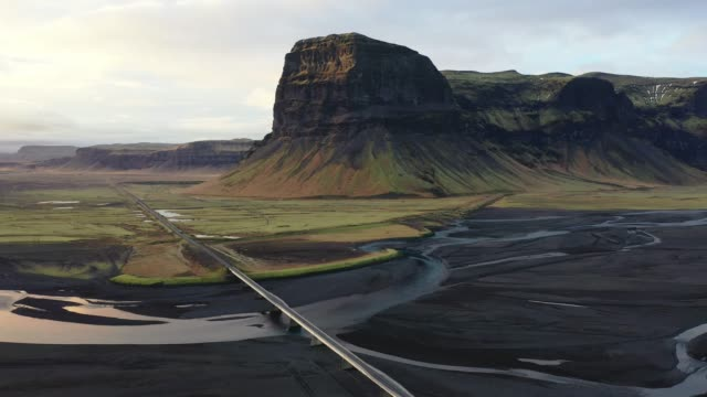 scenic aerial view of road near the river in iceland - black sand stock videos & royalty-free footage