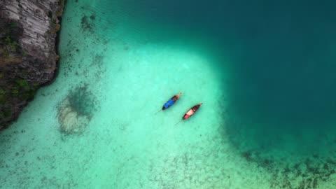 vídeos y material grabado en eventos de stock de panorámica vista aérea de dos barcos en el mar en tailandia - islas phi phi